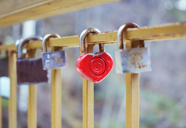 As fechaduras penduradas em uma cerca de metal em uma ponte do amor cadeado em forma de coração