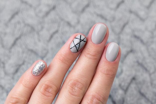 As fêmeas mão na camisola de malha cinza com manicure moderno close-up
