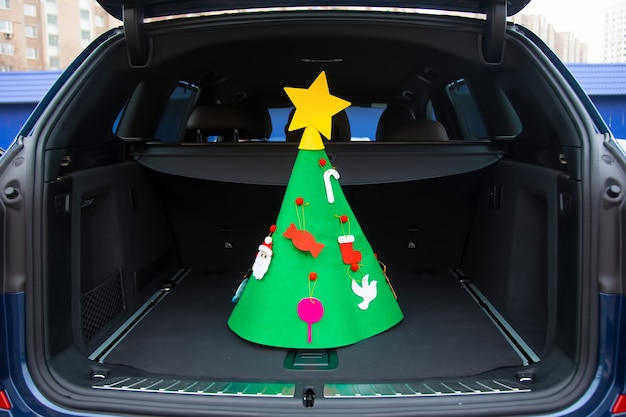As férias estão chegando. uma árvore de natal de feltro decorada com brinquedos e uma estrela fica no centro do tronco vazio de um crossover moderno. close-up, foco suave