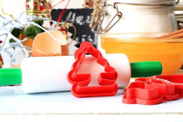 As ferramentas de decoração de natal para assar biscoitos formam um rolo sobre um fundo rústico de madeira claro foco suave estilo rústico