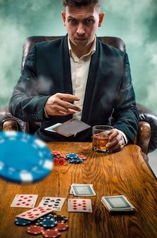 As fichas para apostas, bebida e cartas de jogar na mesa de madeira. conceito de pôquer