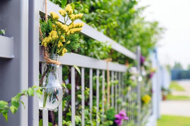 As flores amarelas na ampola deram forma ao vaso que pendura na cerca home.