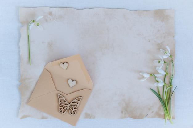 As flores da primavera são snowdrops e papel e envelope para texto em um fundo de madeira
