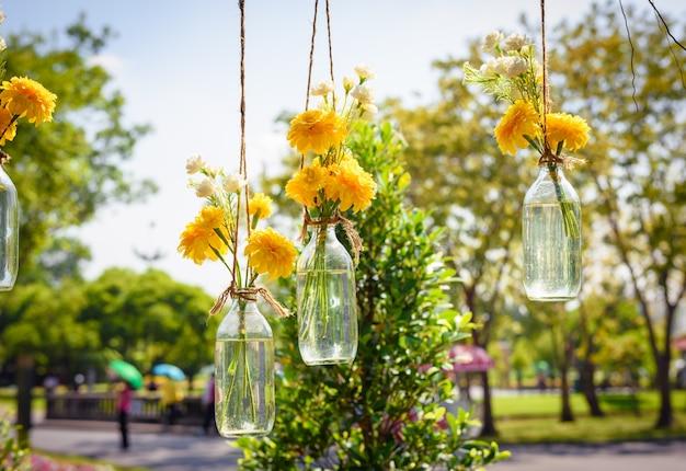 As flores de calêndula em uma suspensão de garrafa de vidro. arranjos de vasos de flores