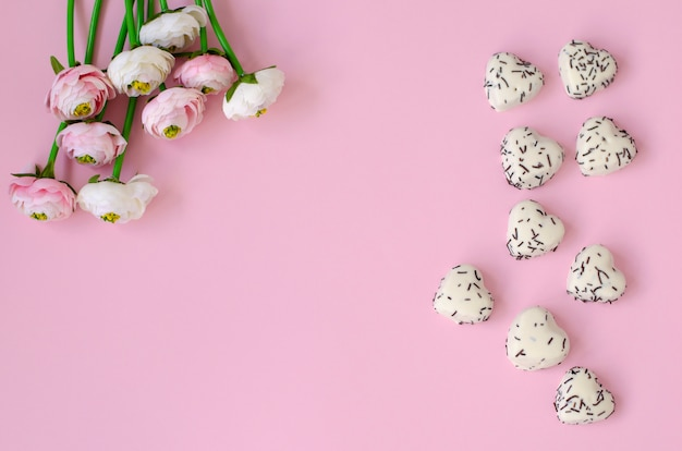 As flores e o coração deram forma a bolinhos no fundo do rosa pastel.