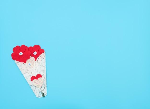 As flores feitas de corações de feltro enroladas em um feixe de renda branca sobre fundo azul
