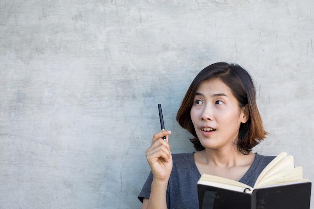 As fofas mulheres asiáticas estão pensando em algo com seu livro sobre fundo cinza