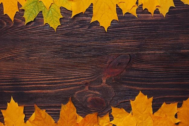 As folhas de outono como moldura estão em madeira, copie o espaço