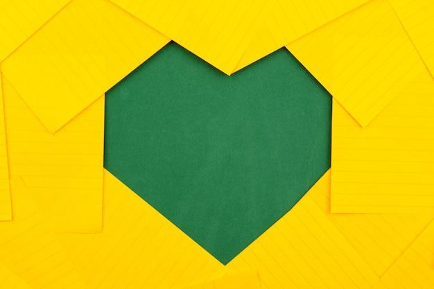 As folhas de papel alaranjadas encontram-se em uma placa de escola verde e dão forma a uma forma do coração do quadro.