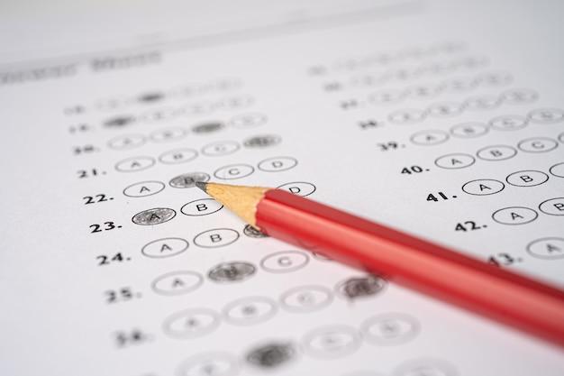 As folhas de respostas com desenho a lápis são preenchidas para selecionar a opção.