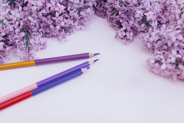 As folhas do papel e da mola limpos brancos florescem o lilás, em um fundo do fundo da cor.