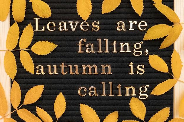As folhas estão caindo, o outono está chamando, citação motivacional no quadro de avisos e folhas de outono amarelas