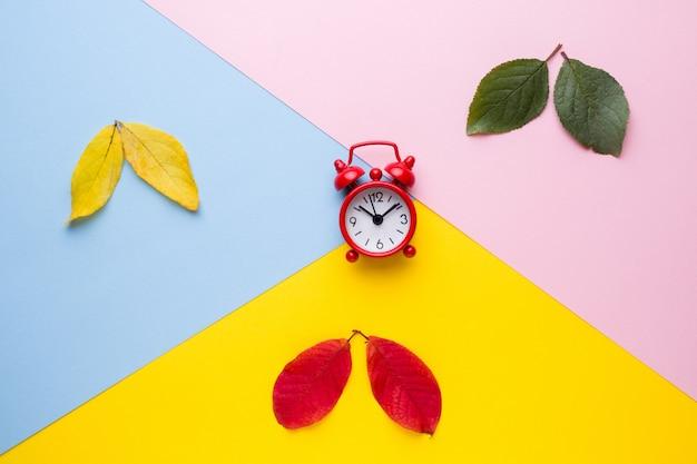 As folhas são verde, amarelo e vermelho tempo, despertador no relógio