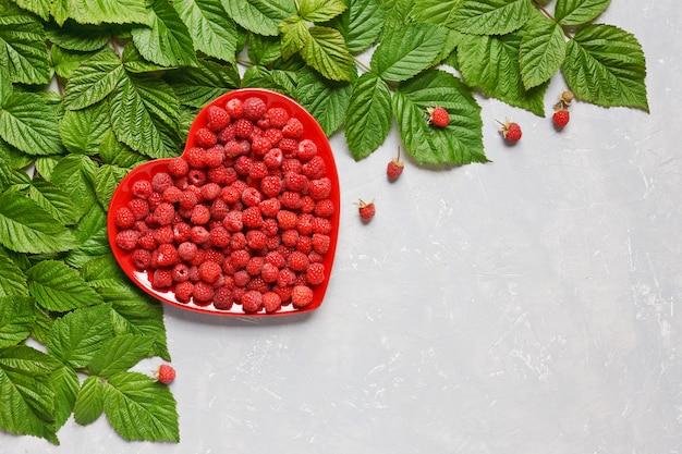 As framboesas suculentas frescas no coração vermelho deram forma à placa e ao teste padrão das folhas da framboesa.