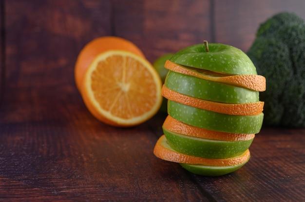 As frutas são dispostas em camadas com maçãs e laranjas.