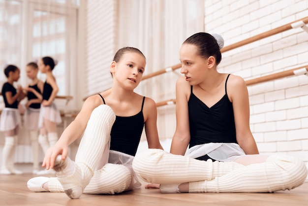 As garotas se comunicam na escola de balé.