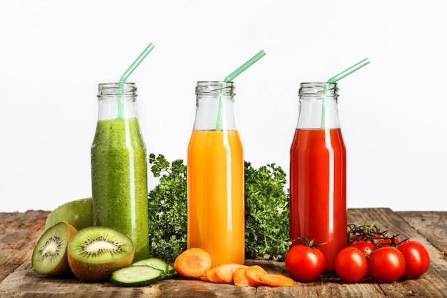 As garrafas com sucos de frutas de kiwi e vegetais frescos na mesa de madeira. dieta de desintoxicação.