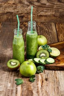 As garrafas com sucos de vegetais frescos na mesa de madeira