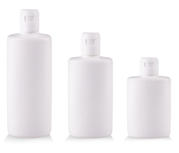 As garrafas de plástico brancas com sabonete ou shampoo sem rótulo refletem no fundo branco