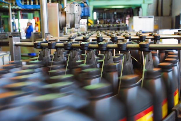 As garrafas são transferidas no sistema de correia transportadora. máquina industrial para fábrica de óleos lubrificantes automotivos. conceito industrial e de tecnologia.