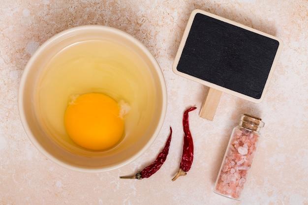 As gemas e a proteína do ovo em uma tigela com pimenta; sal do himalaia e cartaz em branco
