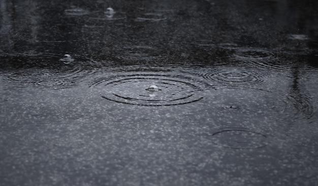 As gotas de chuva espirrando durante a chuva forte caem à noite. foco seletivo e profundidade de campo rasa.