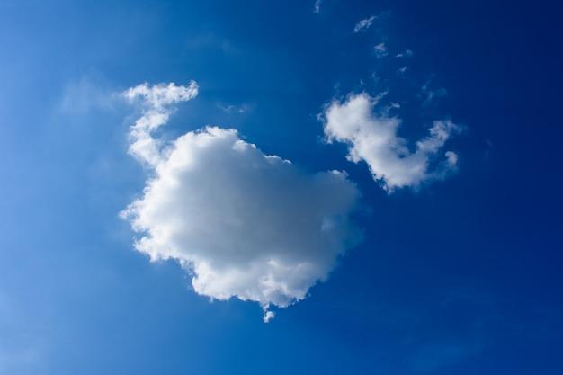 As grandes e pequenas nuvens no céu azul e bom dia de manhã