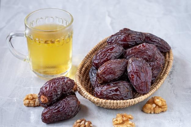 As grandes frutas da tâmara (medjool) na cesta com nozes e chá no chão de mármore.