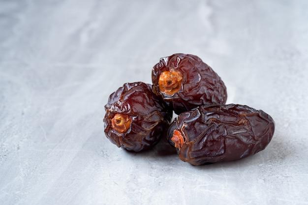 As grandes frutas tâmaras (medjool) em um piso de mármore.