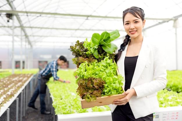As hortaliças frescas são colhidas por agricultoras asiáticas em fazendas com sistema de plantas hidropônicas na estufa e vendidas. vegetais frescos e o conceito de comida saudável.