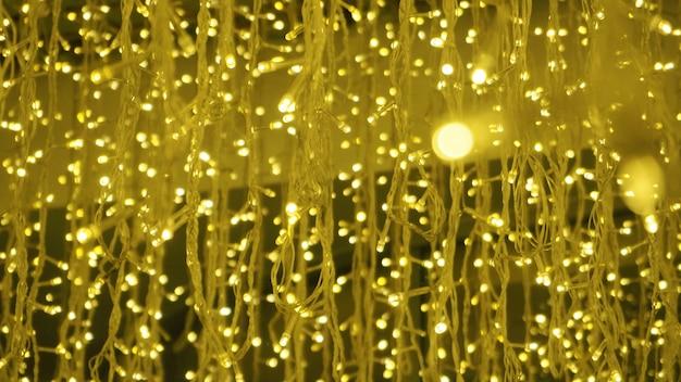 As imagens do bokeh circundam as bolhas que dão forma à cor amarela de uma pequena lâmpada led durante a noite.