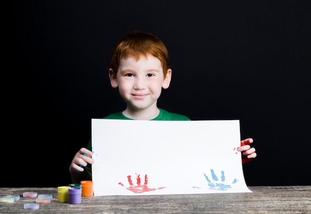 As impressões digitais da criança em uma folha de papel branca enquanto desenha com as mãos da criança usando tintas multicoloridas