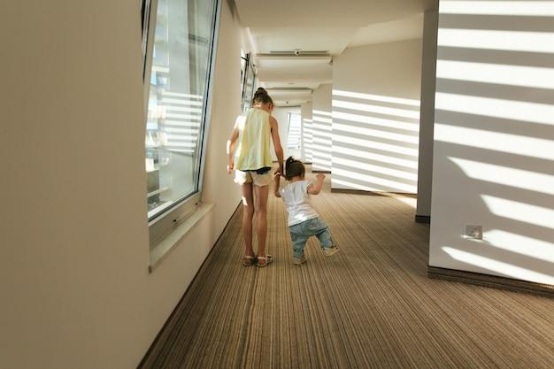 As irmãs meninas no corredor do hotel se alegram com o sol que brilha através das cortinas.