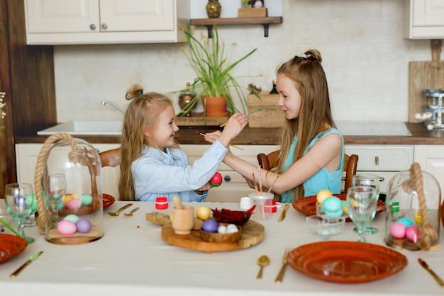 As irmãs pintam ovos de páscoa