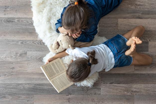 As irmãzinhas estão lendo um livro com um ursinho de pelúcia deitado no chão, na vista de cima do quarto.