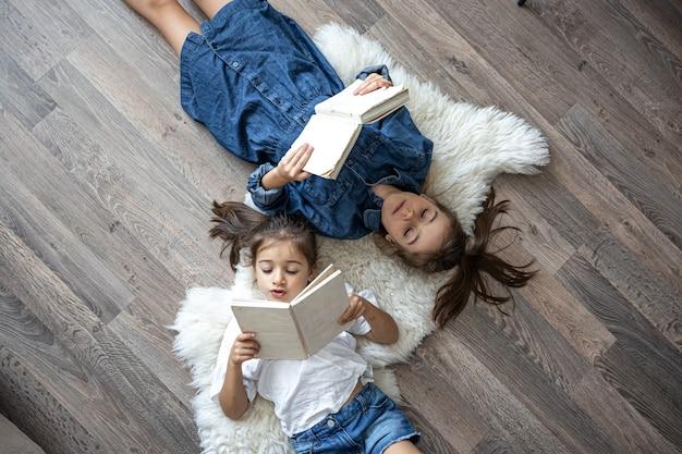 As irmãzinhas lêem livros caídos no chão, vista de cima.