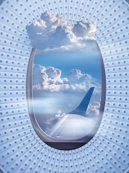 As janelas da aeronave se enquadram como um telhado do estádio com bela vista aérea do céu nublado azul claro e da asa do avião, com espaço de cópia. conceito de viagens e transporte.