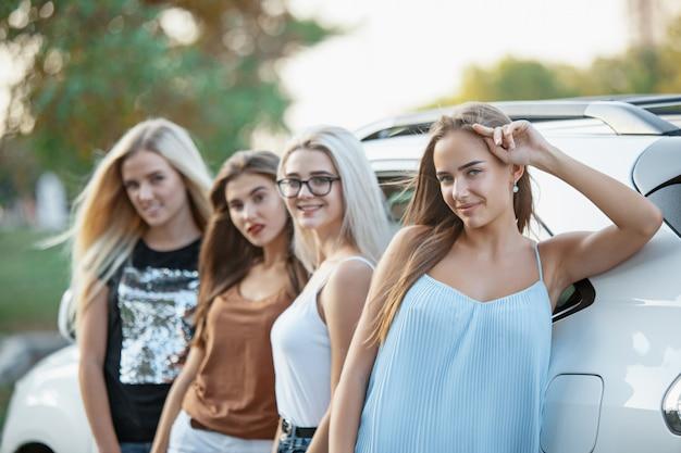 As jovens em pé perto do carro
