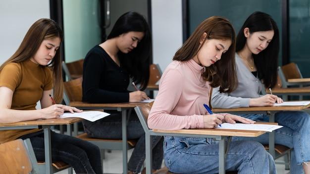As jovens estudantes universitárias se concentram em fazer os exames em sala de aula. as alunas gravam seriamente o exercício dos exames em sala de aula.