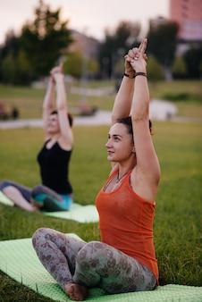 As jovens fazem yogoutdoors no parque durante o pôr do sol. estilo de vida saudável.