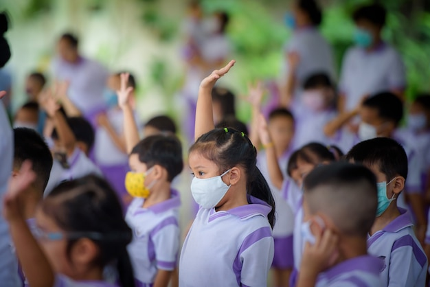 As jovens garotas asiáticas no jardim de infância, as escolas na tailândia usam máscaras protetoras. o vírus covid-19 fica na linha e distanciamento social