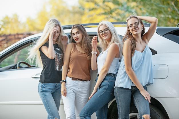 As jovens mulheres em pé perto do carro