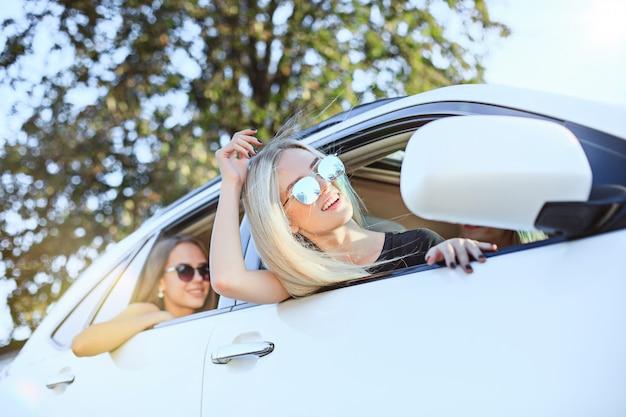 As jovens mulheres no carro sentado e sorrindo ao ar livre. o estilo de vida, viagens, aventura e conceito de amizade feminina