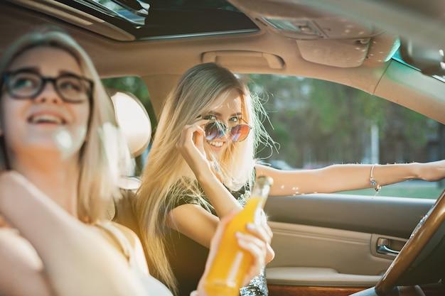 As jovens no carro sorrindo