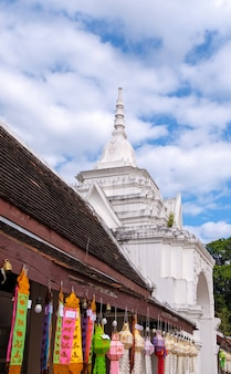 As lanternas de papel coloridas estão penduradas ao redor do pequeno corredor perto da câmara de entrada da igreja tailandesa. (área pública não necessária liberação de propriedade), vista frontal com o espaço da cópia.
