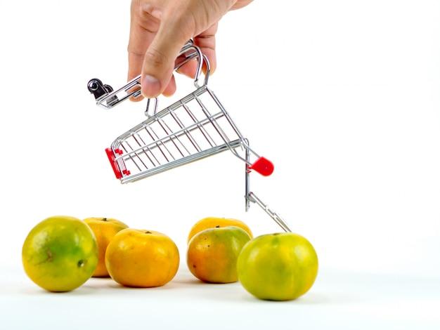 As laranjas frescas e carrinho de compras, conceito de compras de cesta com fundo branco