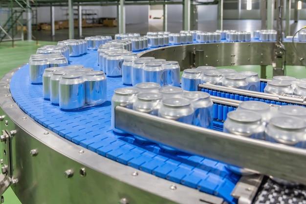 As latas de bebidas de alumínio para bebidas movem-se na correia transportadora na grande fábrica.