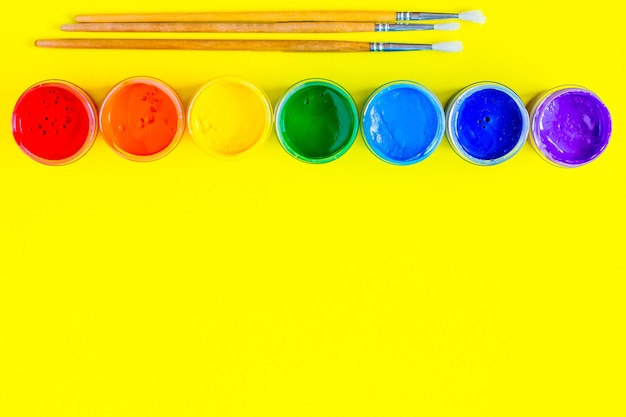 As latas de tinta estão alinhadas no topo as cores são exibidas na ordem do arco-íris existem pa ...