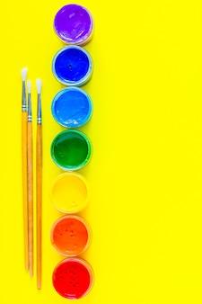 As latas de tinta ficam alinhadas do lado em que as cores são exibidas na ordem do arco-íris ali ...