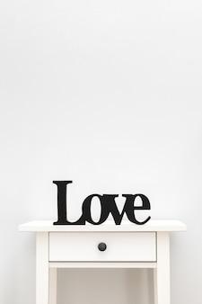 As letras pretas amam de uma árvore em uma tabela branca. cortar a carta de madeira. letras de amor em um fundo branco